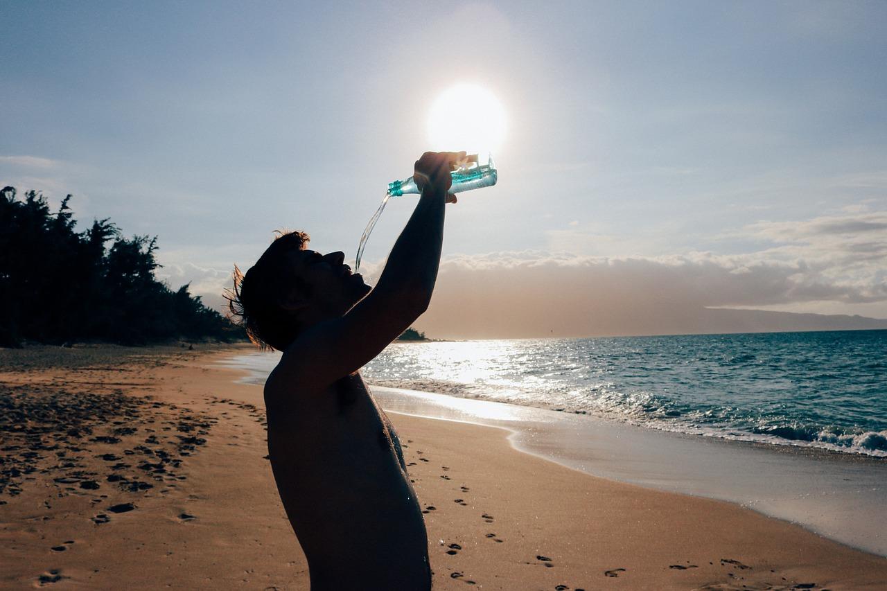 chlap pije vodu na plazi